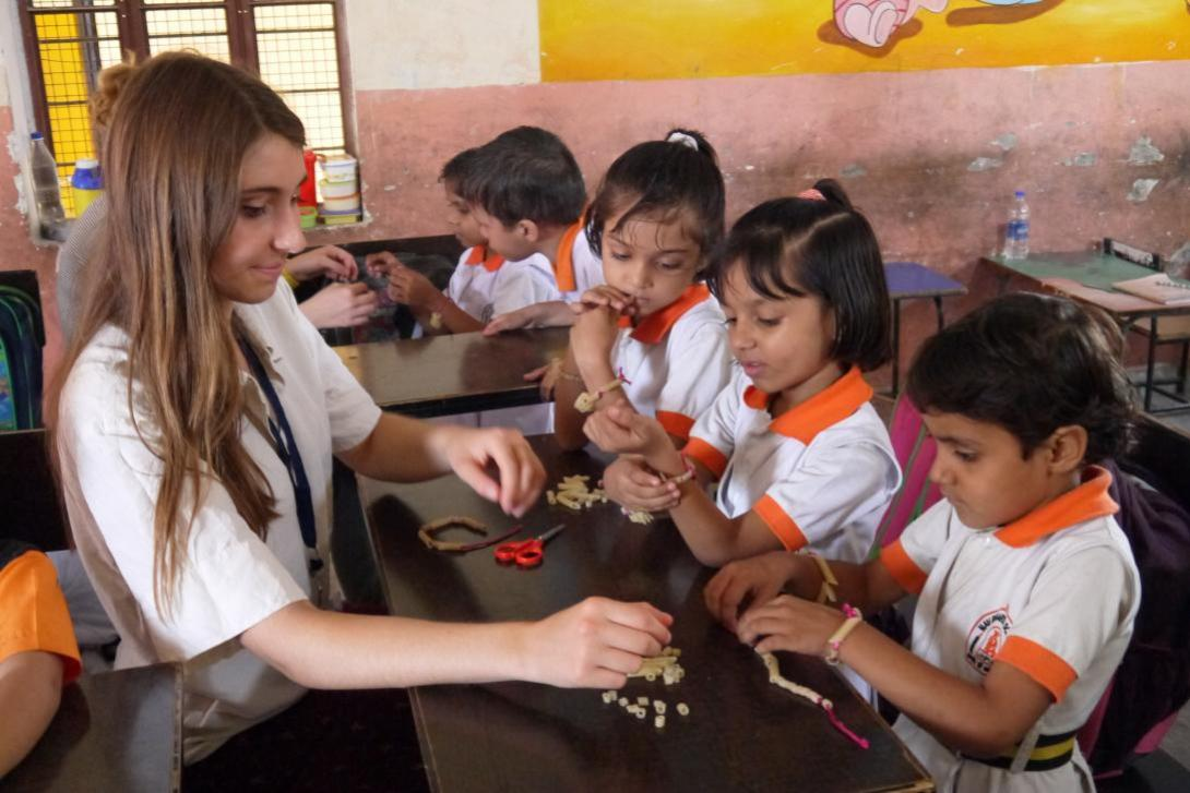 Childcare volunteer in India does arts and crafts with children in a Jaipur elementary school